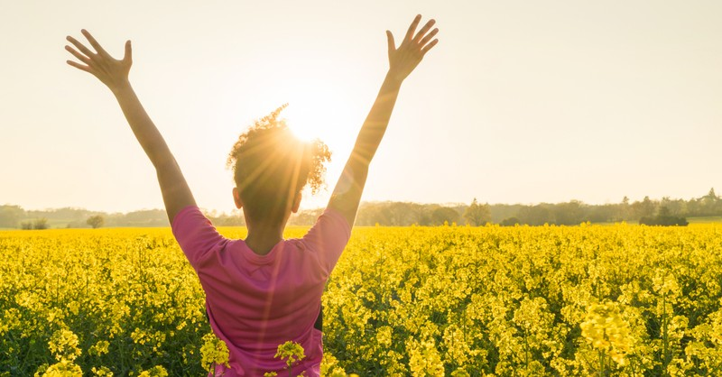 woman arms up in praise celebration gratitude in wildflower field