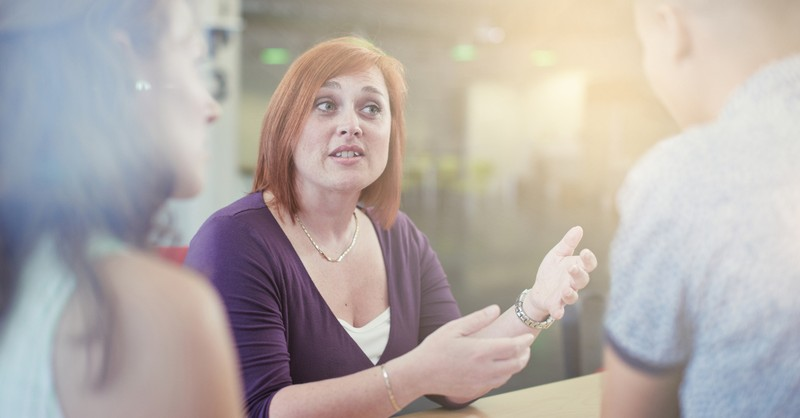 woman talking to others in a serious conversation telling her story