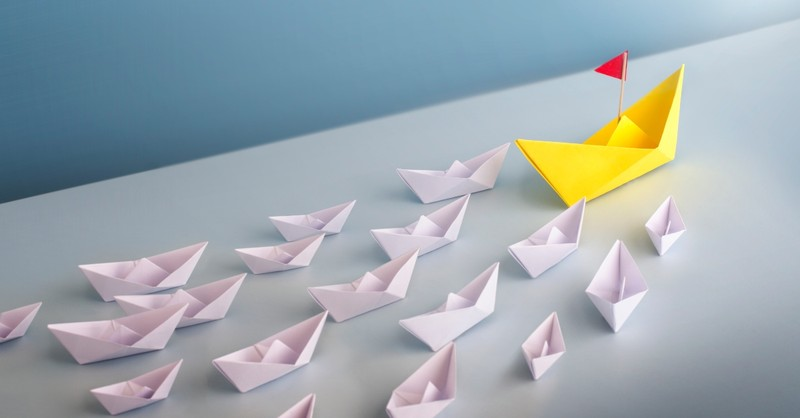 Small paper boats following one leader