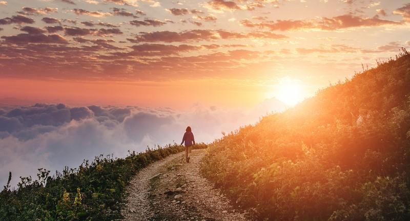 woman hiking on trail around mountian toward sunset