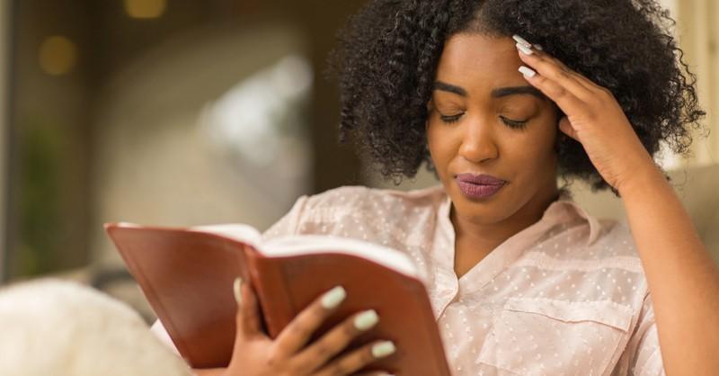 woman upset reading bible