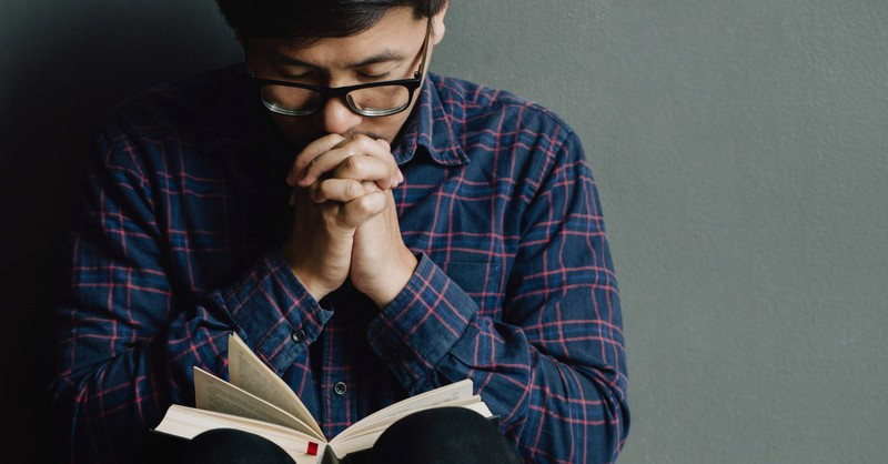 man eyes closed praying with Bible open on lap, whatever you ask in Jesus' name