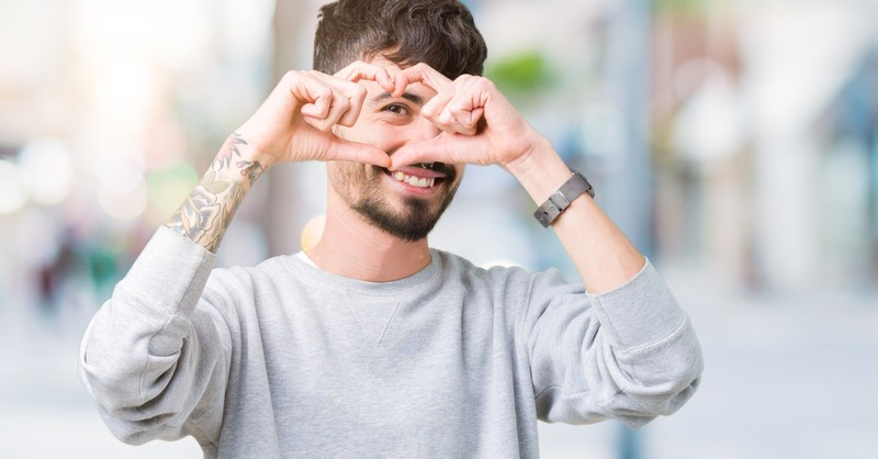 man making heart sign with hands tattoo on arm