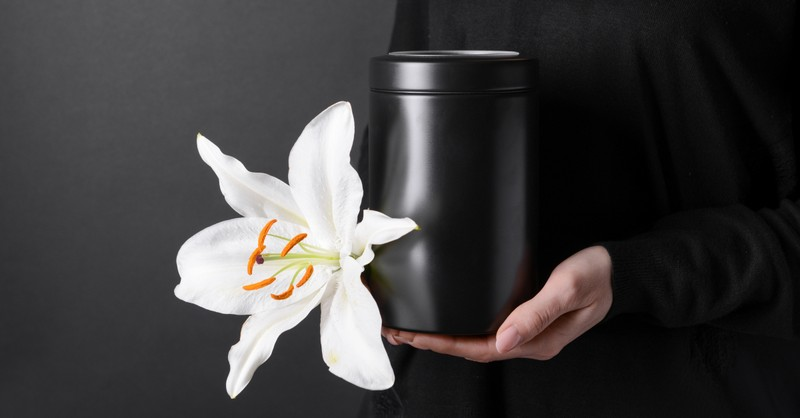 woman holding cremation urn with white lily flower on dark background