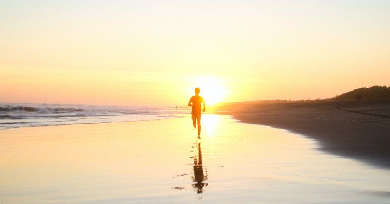 boy running down beach toward sunset at dusk