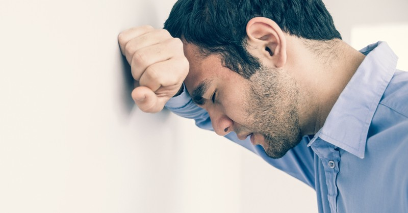 man concerned with head against wall in serious prayer to help my unbelief
