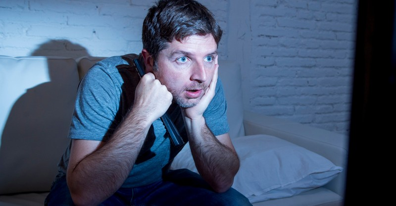 man addicted to television news staring
