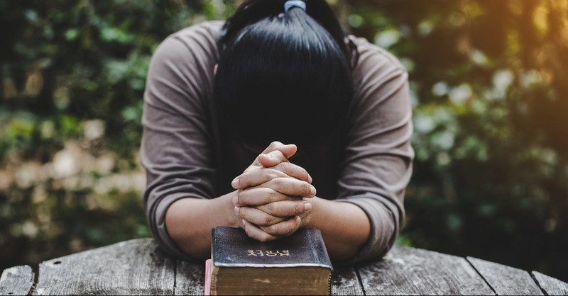 Woman praying over a Bible
