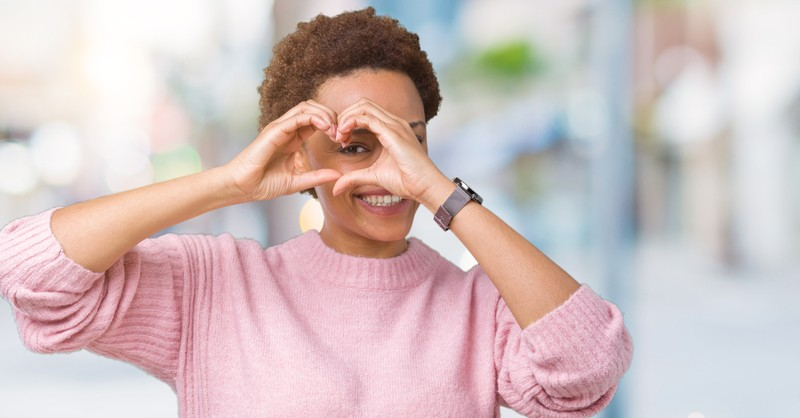 woman making heart with hands over eye to signify apple of my eye