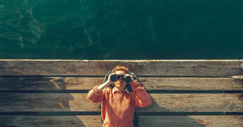 Woman looking up with binoculars