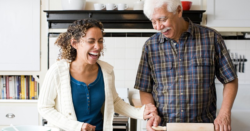 senior dad and adult daughter baking together laughing