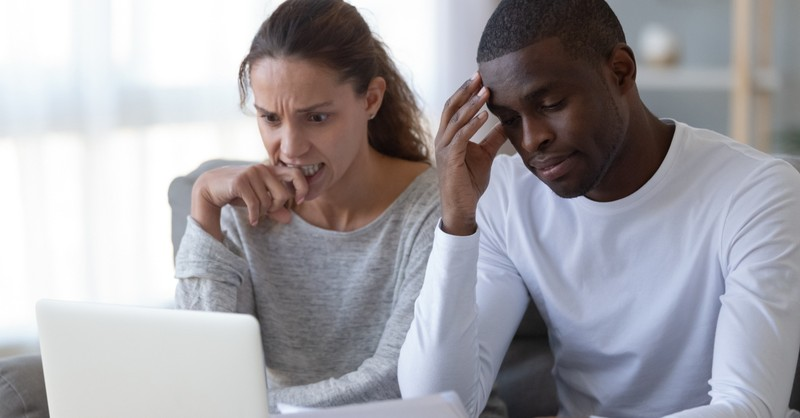 couple stressing over money anxiety at laptop due to COVID-19