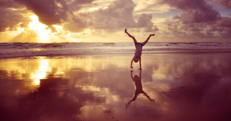girl and reflection doing cartwheel on beach at sunset, flipping the switch
