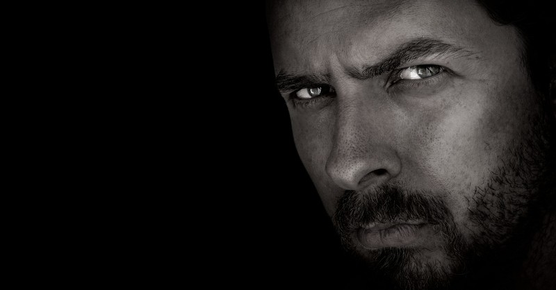 sinister and serious close up of man's expression in black and white, what should a wife do when a husband is cruel
