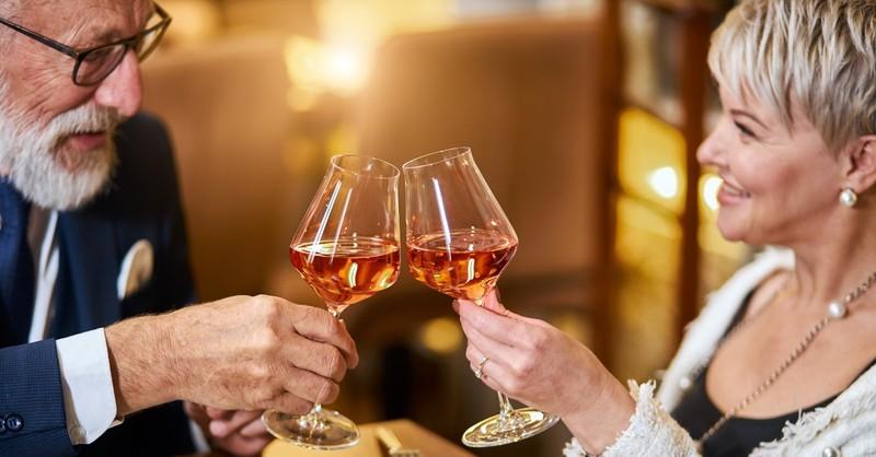 senior couple on dinner date having wine