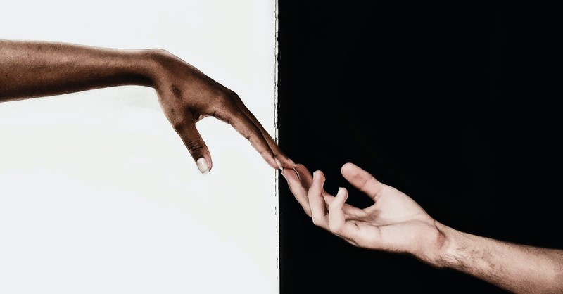 black and white hands reaching out to each other, reasons you might be uncomfortable talking about race