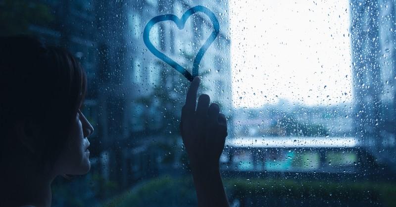 woman tracing heart on window on rainy day