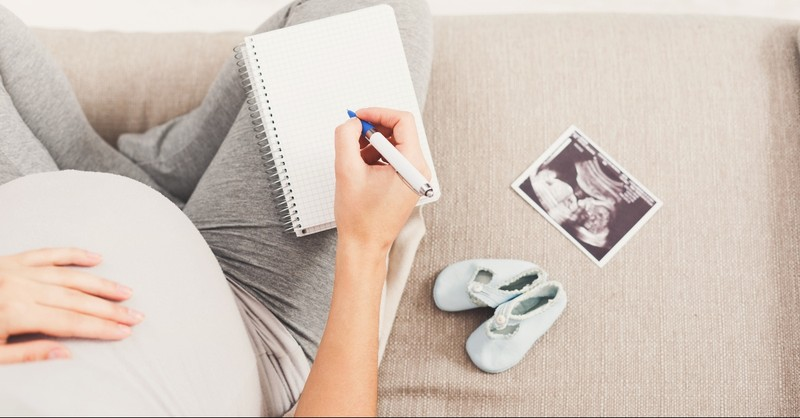 Pregnant woman on the couch with a sonogram and journals