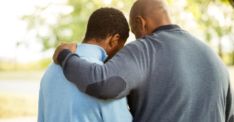 dad with arm around teen son apologizing hugging or praying