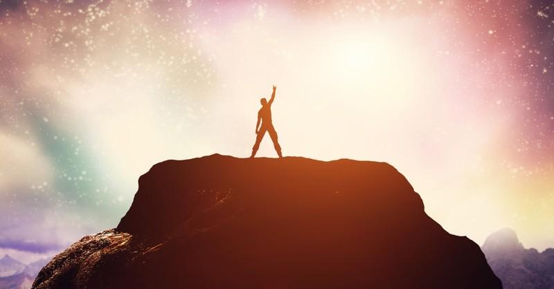 confident brave man fist pump on mountaintop at sunset