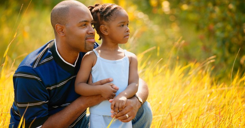 Dad and daughter in yellow field looking forward visioning future