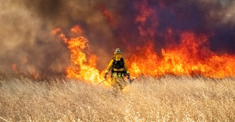 fire fighter standing in front of flames in grassy field, prayer for california fires