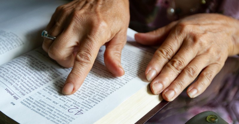 mature senior hand reading bible page