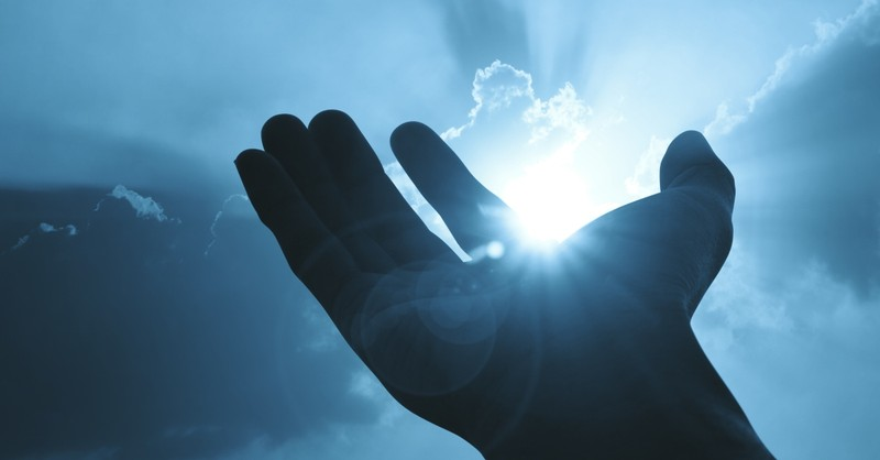 hand open up to sunburst through cloud in praise to God