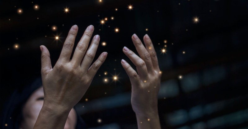 woman hands up in worship little lights sparkling