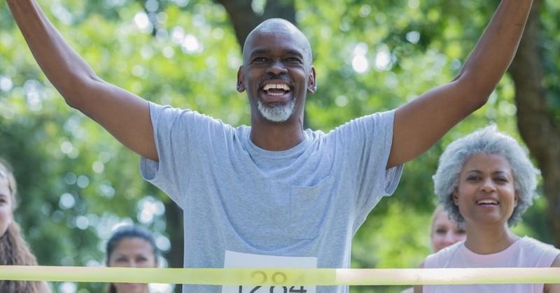senior athletic man crossing race finish line joyful celebration