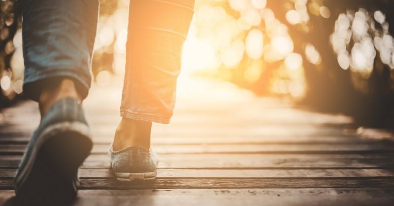 Feet walking across a wooden bridge