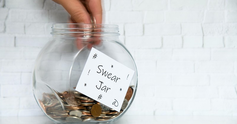 person putting coins into a swear jar, is cursing a si