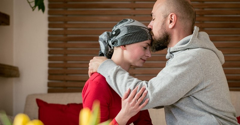 husband kissing wife in cancer treatment on forehead