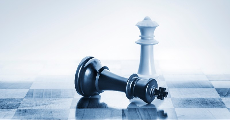 King chess piece fallen over before the queen piece