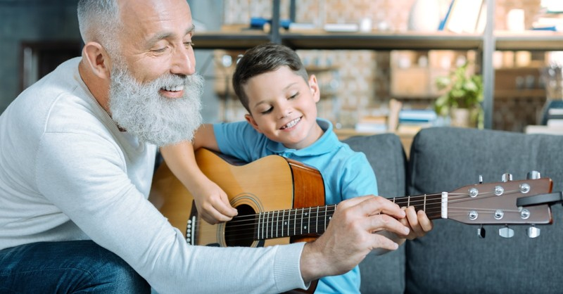 senior man teaching young boy how to play guitar in retirement