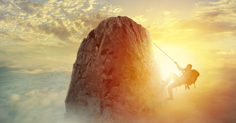 man climbing mountain peak to signify with great power comes great responsibility