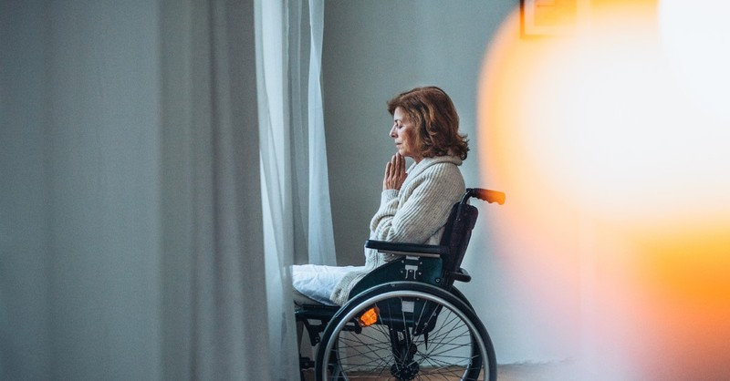A woman seated in a wheelchair prays fervently before a window