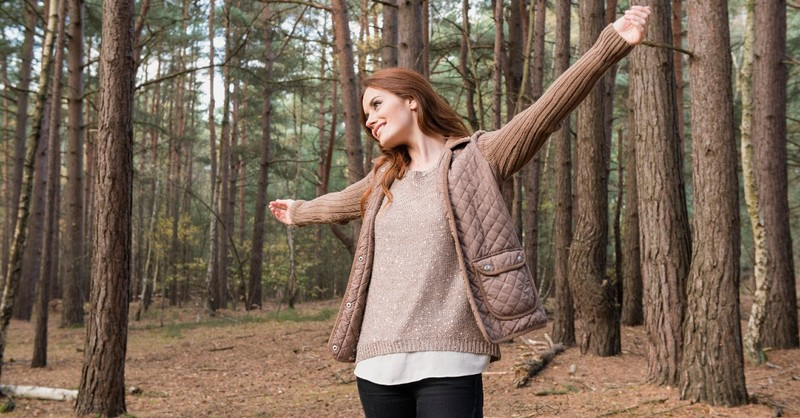 A young woman spreads her arms wide in the forest, communing with God and nature