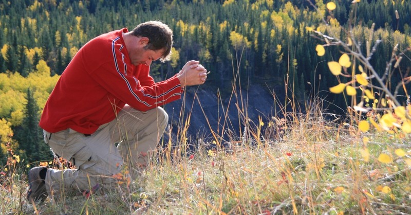 man bowing down in prayer outdoors lead with integrity