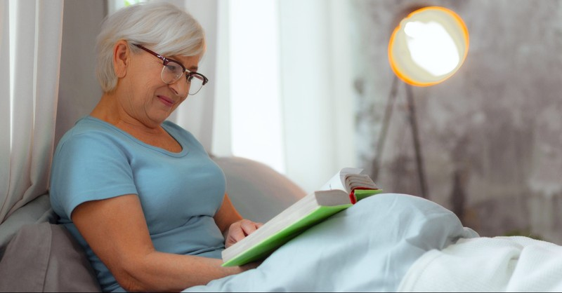 Elderly woman reading the Bible in bed