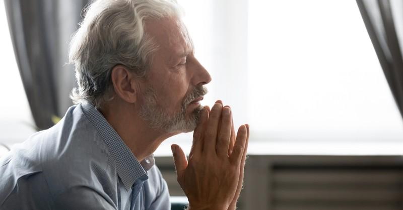 senior man in prayer for abundant life