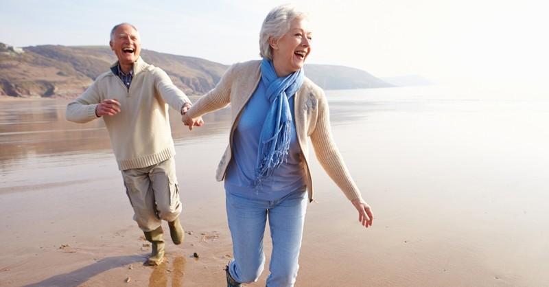 happy senior couple running along beach