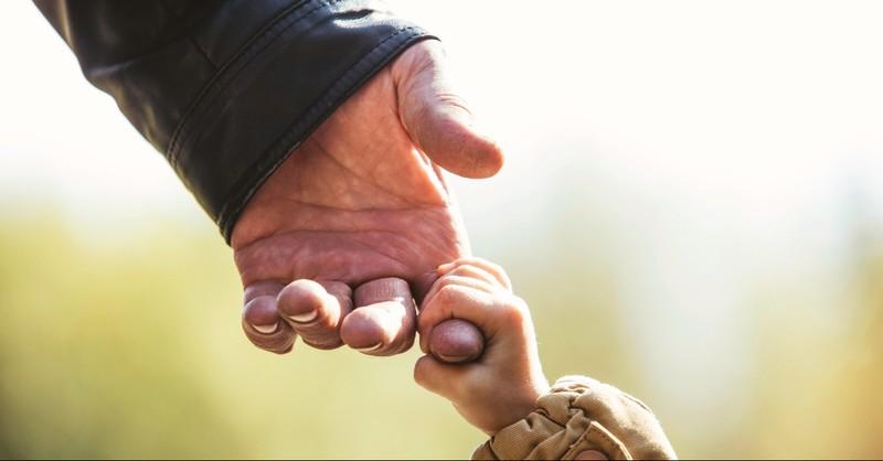 Grandchild holding grandparent's finger