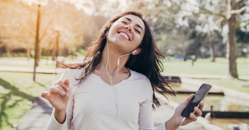 woman joyfully listening to music on headphones walking in park