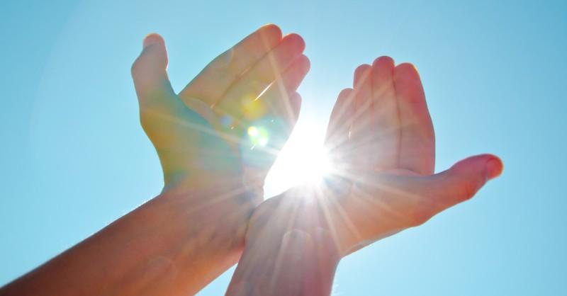 hands up to bright sun bursting through