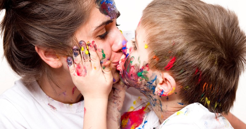 toddler kissing mom with messy paint hands and faces
