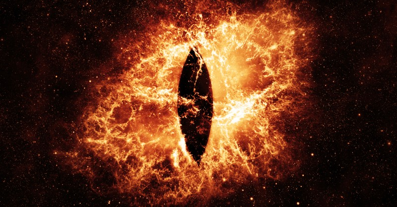 closeup of reptilian eye in flames to signify 7-headed dragon in end times revelation