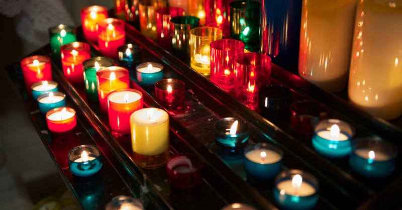 many candles lit in church to represent All Souls Day
