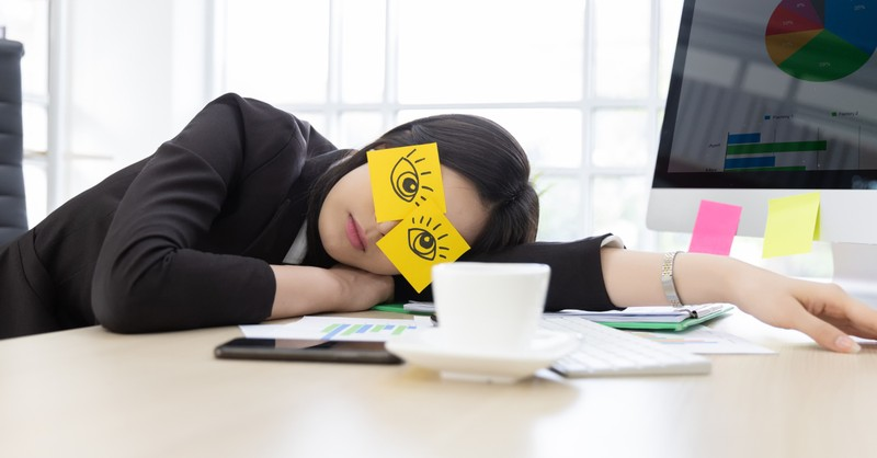 woman exhausted at computer with awake eyes post-it notes over her eyes