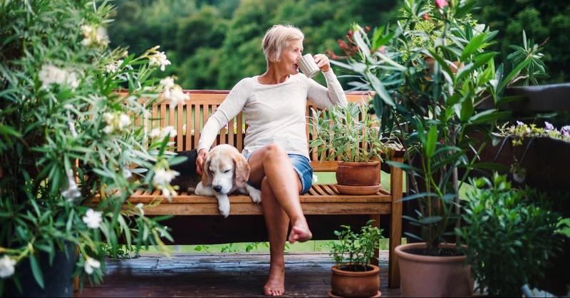 Elder woman drinking coffee with her dog in her garden